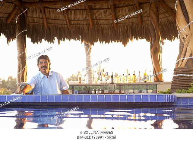 Hispanic bartender working near poolside