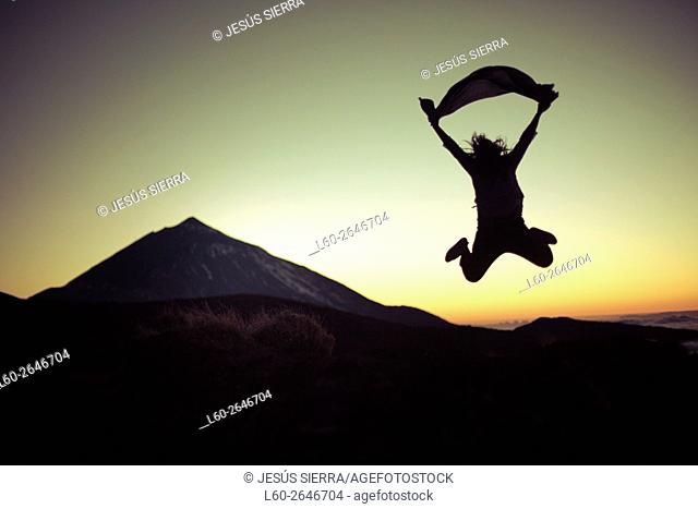 Young woman jumping in Parque Nacional del Teide, Tenerife, Canary Islands, Spain