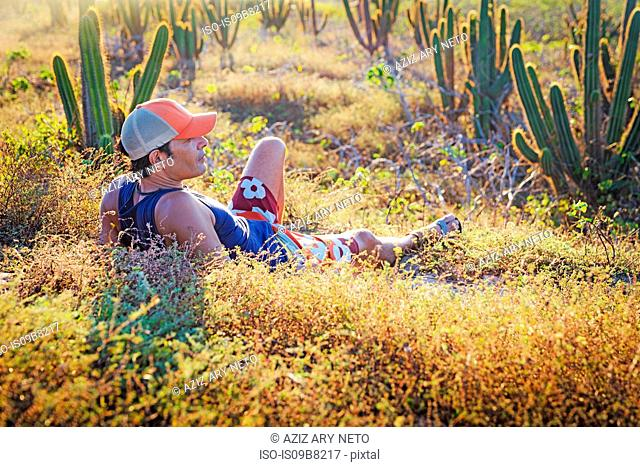 Man relaxing in grass, surrounded by cacti, Jericoacoara National Park, Ceara, Brazil