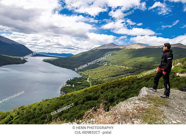 Woman in motorbike clothes is looking over lake in Tierra del Fuego, Argentina