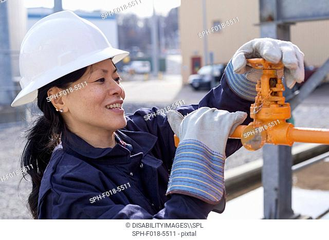 Female power engineer checking valve at power station