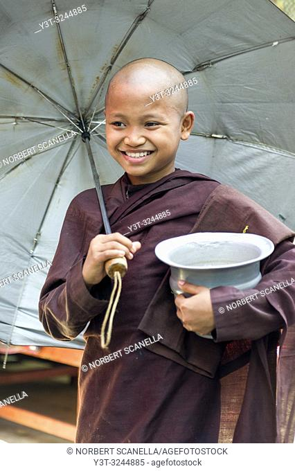 Myanmar (formerly Burma). Mon State. Mawlamyine (Moulmein). Young novice with umbrella giving alms