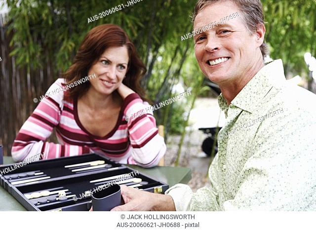 Mature man and mature woman playing backgammon