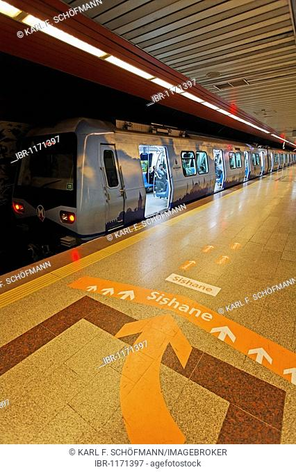 Subway is waiting with open doors on the platform, a large directional arrow on the floor, modern subway station, Taksim Square, Beyoglu, Istanbul, Turkey