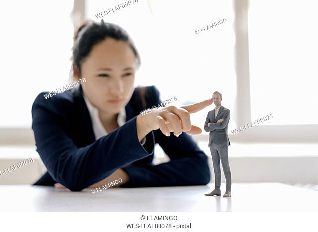 Businesswoman watching businessman figurine, standing on her desk