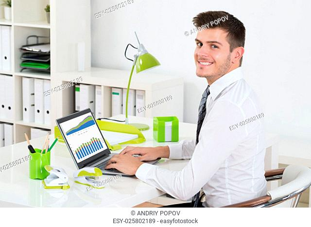Young Businessman Analyzing Graph On Laptop In Office