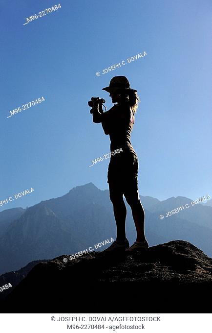 Woman standing on rock with binoculars, Alabama Hills, California, USA