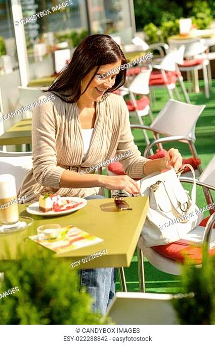 Woman looking in purse at cafe bar