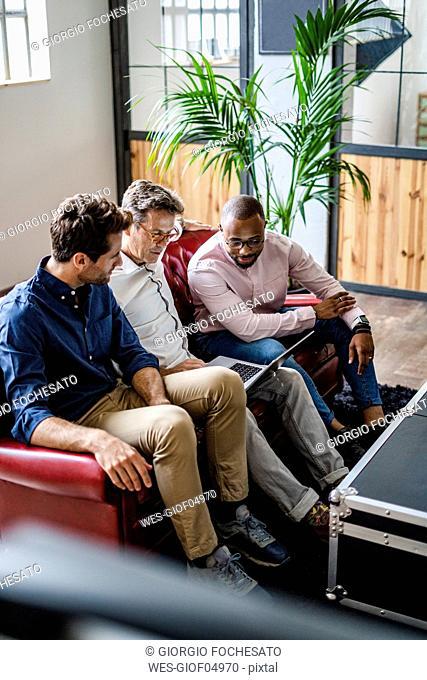 Three businessmen using laptop sitting on sofa in loft office