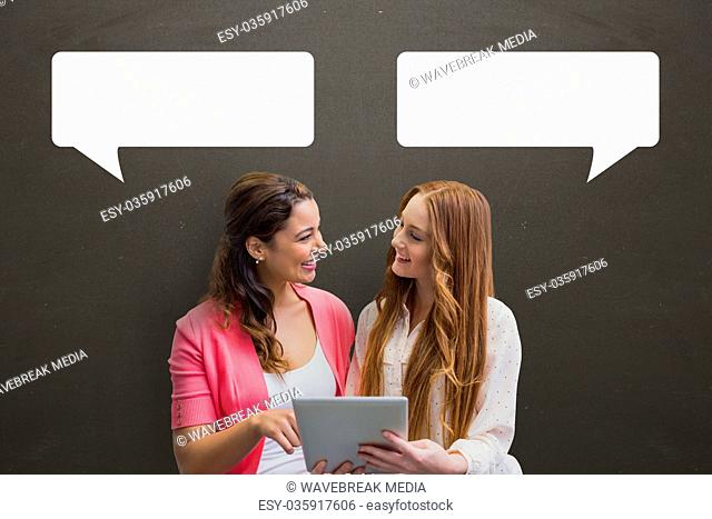 Business women with speech bubbles holding a tablet against grey background
