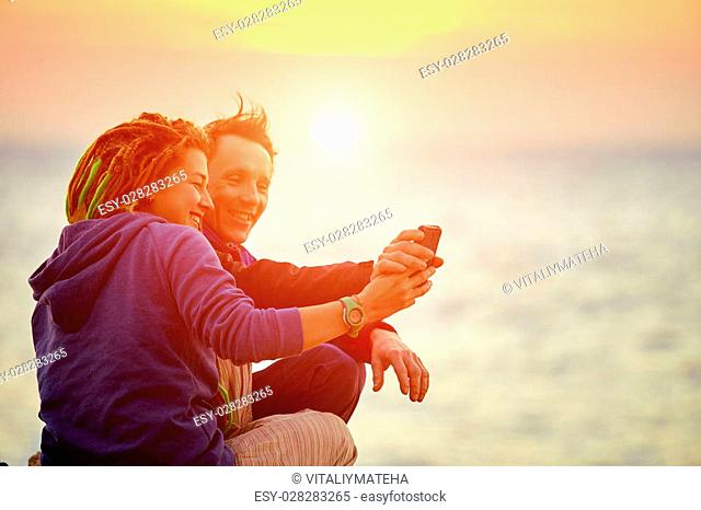 couple standing on the cliff and making selfie against sea and sunrise sun at early morning