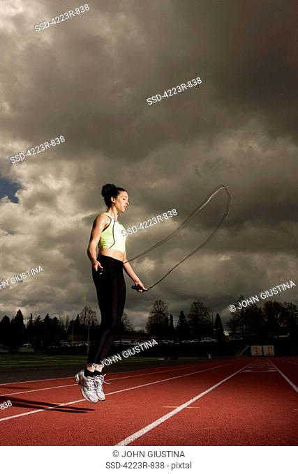 Woman jumping rope on track