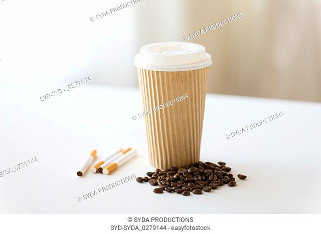 close up of cigarettes, coffee cup and beans