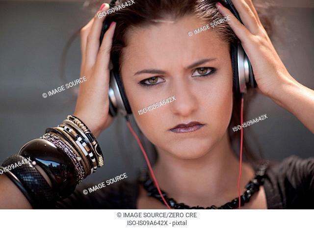 Angry teenage girl wearing headphones