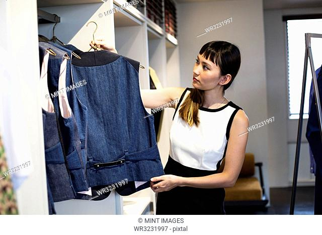 Japanese saleswoman standing in clothing store, hanging blue waistcoats on rail