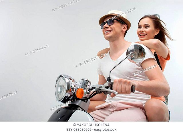 This is a real freedom. Portrait of cute young loving couple traveling by scooter with pleasure. They are sitting and smiling happily