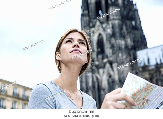 Germany, Cologne, portrait of young woman with city map in front of Cologne Cathedral
