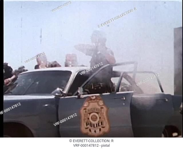 Zoom in to policeman firing gun