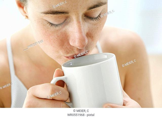 portrait - young woman is drinking tea out of a tea cup