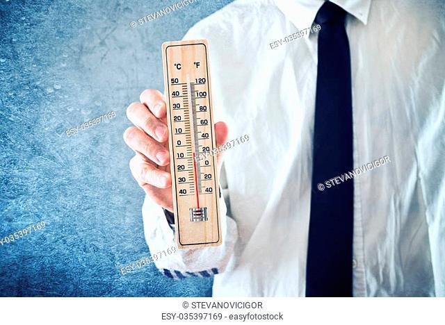 Businessman holding thermometer with temperature on Zero value. Measuring temperature, conceptual image
