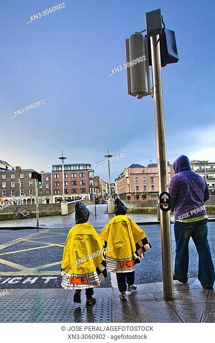Rainy day, two children with raincoat waiting to pass at a traffic light towards a bridge in River Liffey, Dublin city, province of Leinster, Ireland, Europe