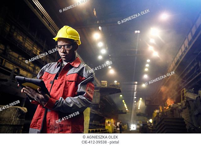 Steelworker using digital tablet in steel mill