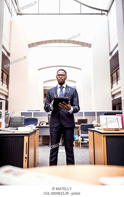 Portrait of young businessman using digital tablet in office