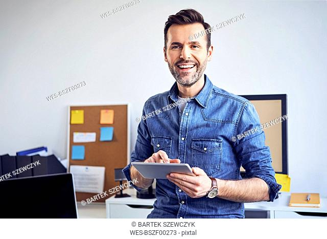 Portrait of smiling man using tablet in office