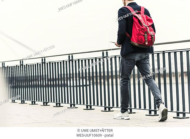 Young businessman walking in the street, carrying digital tablet and backpack