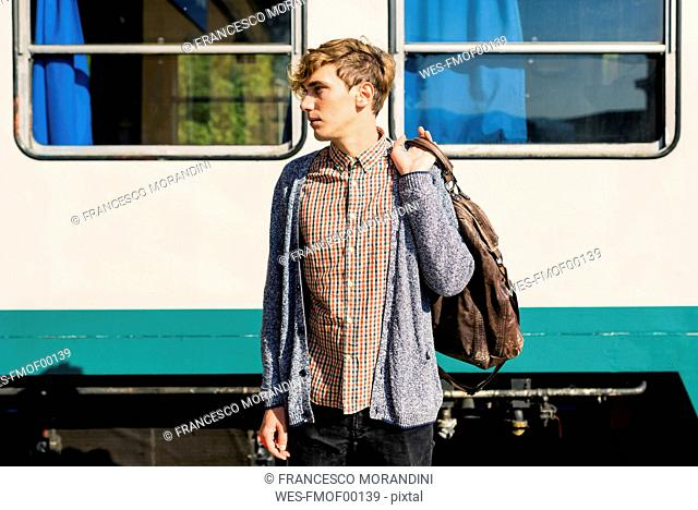 Young man with leather bag standing in front of a train