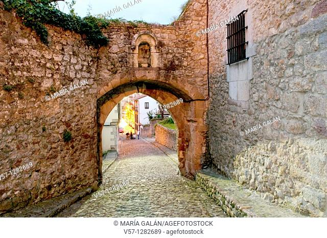 Gate and street in the old town, night view. San Vicente de la Barquera, Cantabria province, Spain
