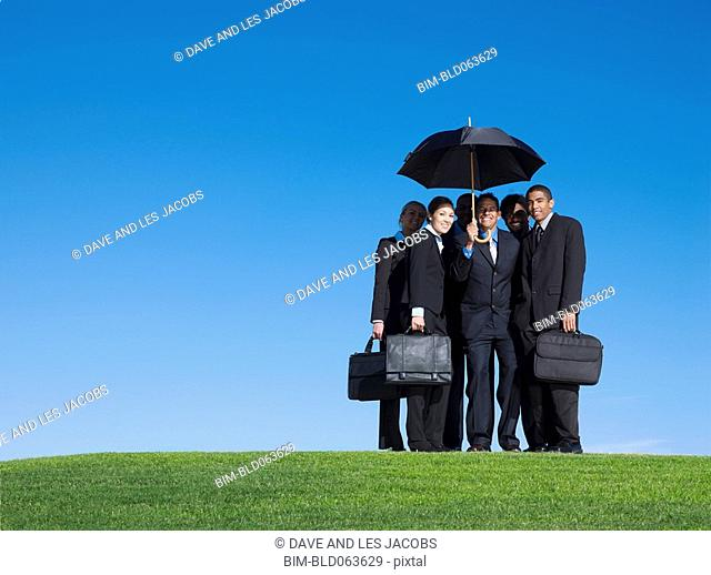 Business people standing outdoors in grass under umbrella