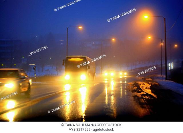 Headlights of cars and a coach bus reflect on wet road on a foggy, blue winter evening in a suburban area. Salo, Finland