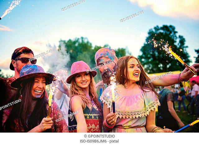 Young adults covered in coloured chalk powder dancing with sparklers at festival