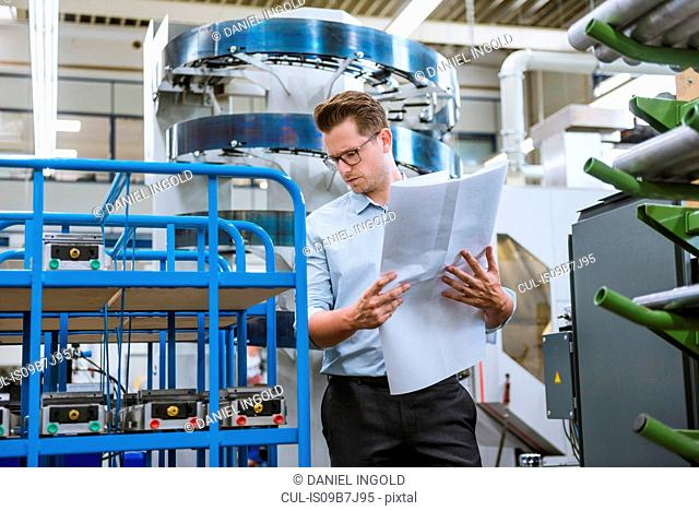 Manager looking at blueprint in factory