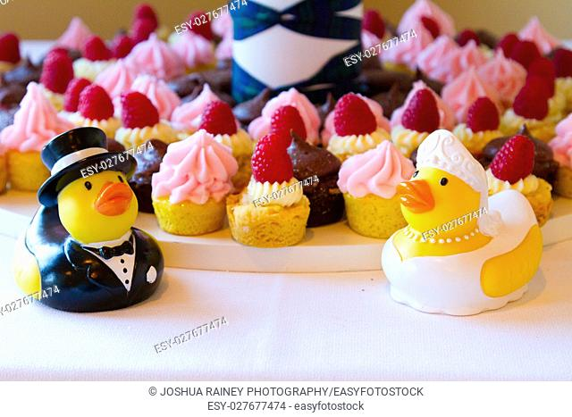 Cupcakes at a wedding reception with rubber duckies in front