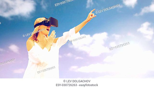 augmented reality, gaming, technology and people concept - amazed young woman with virtual reality headset or 3d glasses pointing finger to something outdoors