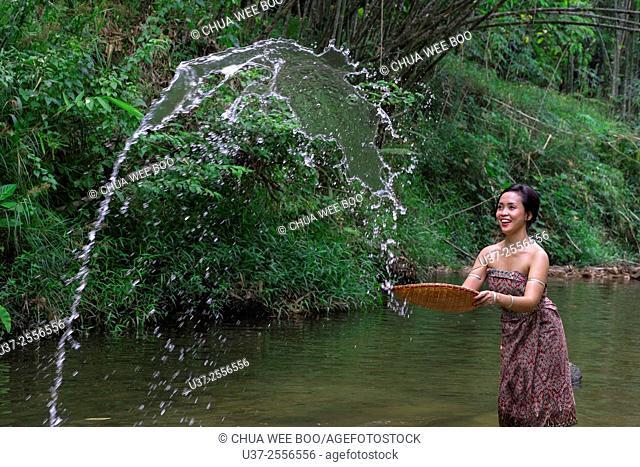 A Bidayuh lady in sarong playing with water, Annah Rais hot spring, Sarawak, Malaysia