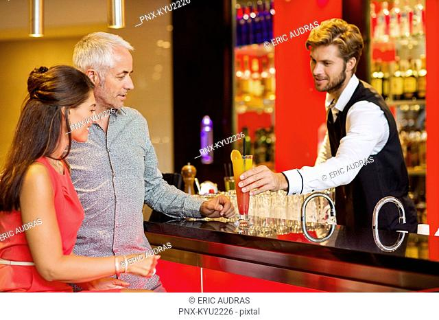 Bartender serving drink to a couple at bar counter