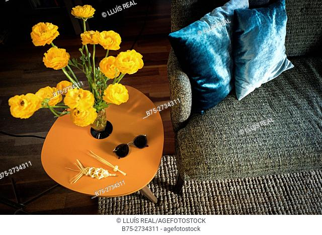 Coffee table with a vase with yellow flowers, a pair of sunglasses and two miniature Easter palms. Part of a sofa with two blue cushions