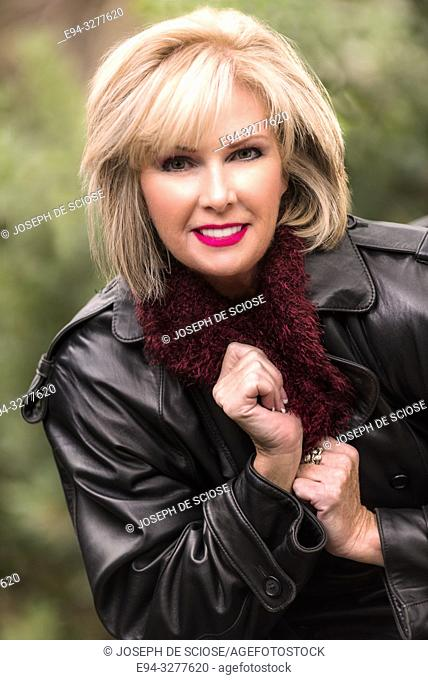 A pretty 59 year old blond woman sitting in a chair outdoors, looking directly at the camera, Alabama