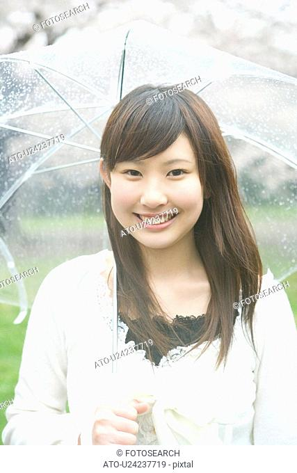 Portrait of a woman holding an umbrella, smiling and looking at camera, front view, Japan