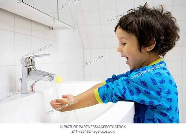 Toddler washing his hands