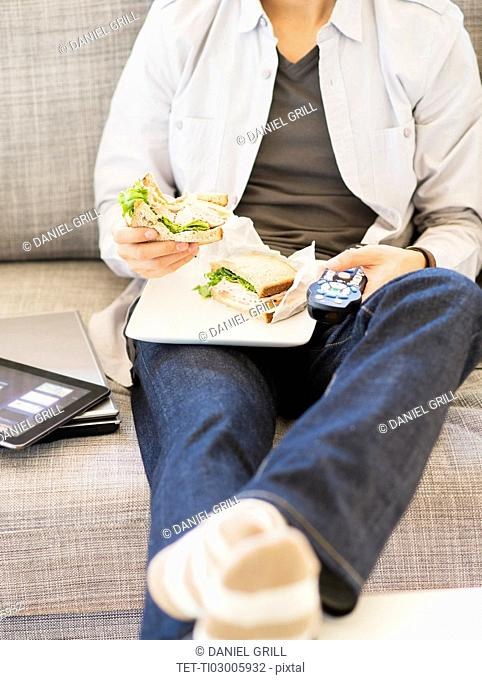 Teenage boy(16-17) eating sandwich and watching tv