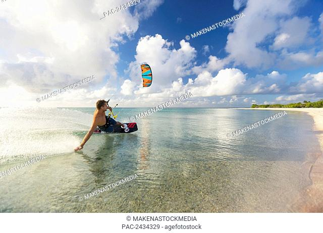 Kiteboarding in tropical lagoon in the South Pacific at sunset; Tikehau, French Polynesia