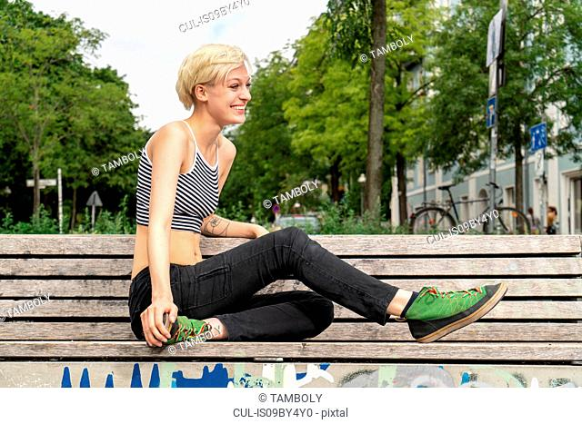 Young woman resting on bench in park