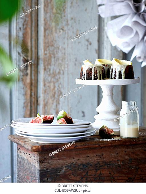 Mini christmas puddings with figs on stack of plates on patio table