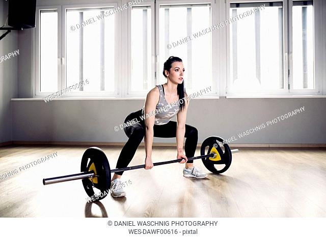Woman preparing for weightlifting in gym