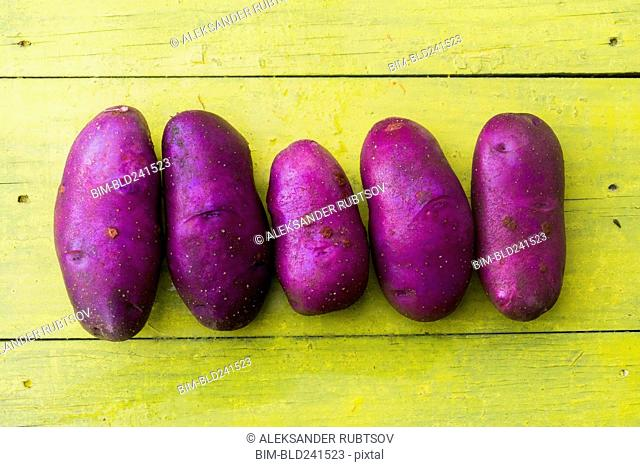 Purple potatoes in a row on wooden table
