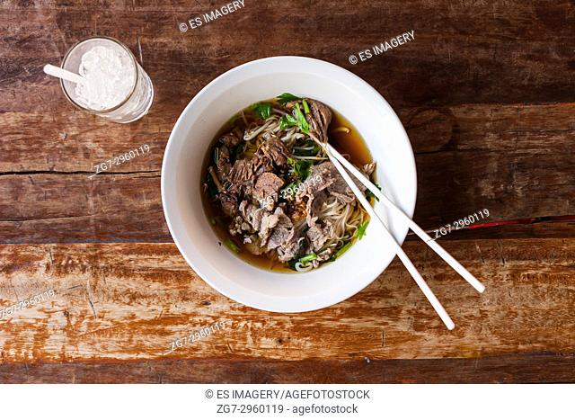 Thai beef noodle soup on a wooden table